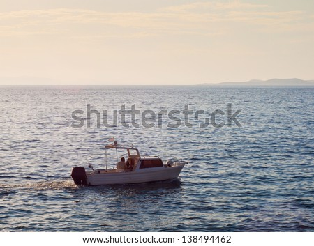 Small yacht in the blue sea off the coast...