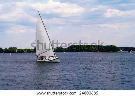 Small yacht on the move - stock photo