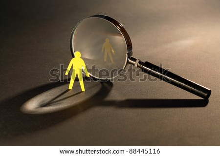 Small yellow paper man standing opposite magnifying glass on dark surface - stock photo