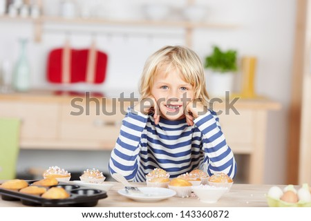 Small young blonde caucasian girl happily smiling while leaning over the kitchen table near a tray of freshly baked muffins - stock photo