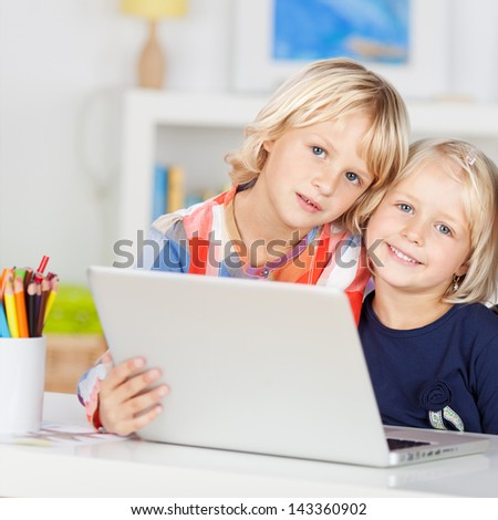 Small young blonde caucasian girls with a happy smile, and wearing colorful clothes, uses a laptop computer - stock photo