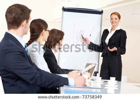 Smart and confident employee pointing at whiteboard while presenting her ideas to business partners - stock photo