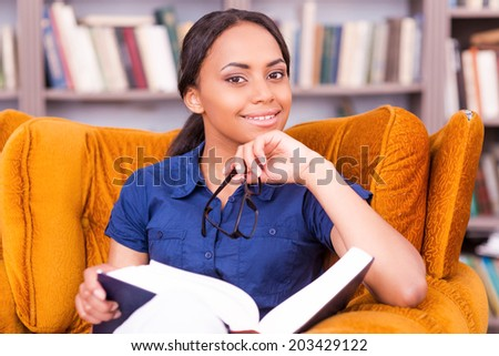 Smart and confident student. Beautiful African female student holding a book and smiling while sitting at the chair in library - stock photo
