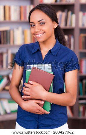 Smart and confident student. Beautiful African woman holding books and smiling while standing in library - stock photo