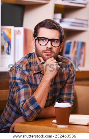 Smart and confident. Thoughtful young man holding hand on chin and looking away while sitting at the desk in library - stock photo