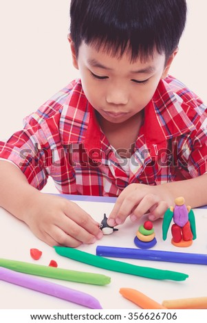Smart asian boy playing and creating toys from play dough. Child moulding whale modeling clay. Strengthen the imagination of child - stock photo