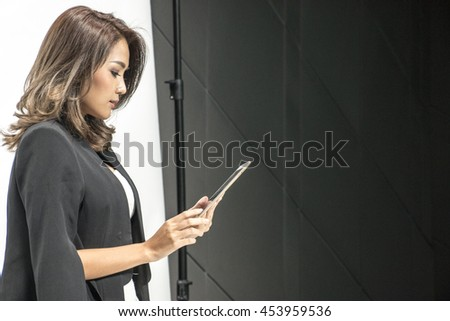 Smart asian woman is looking the tablet in studio - stock photo