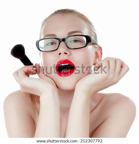 Smart beautiful girl with  a  brushes for makeup wearing black glasses.
