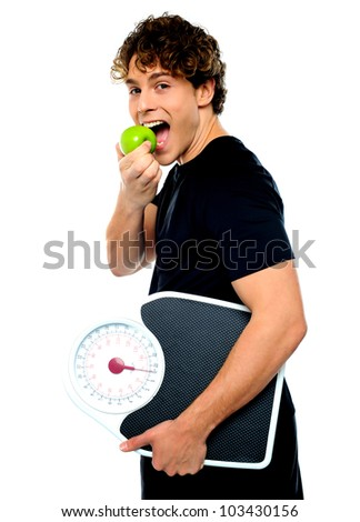 Smart boy eating green apple with scale in his other hand - stock photo