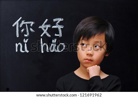 """Smart boy in front of blackboard with Chinese words for """"hello"""" - stock photo"""