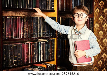 Smart boy stands in the library by the bookshelves with many old books. Educational concept. Science. - stock photo