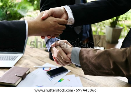 Smart Business handshake for closing the deal after singing the lucrative contract between companies.Trust businessman partner concept.