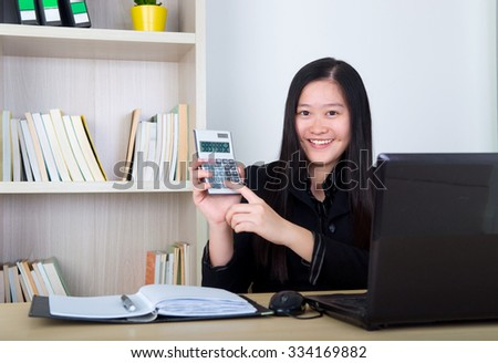 smart business woman showing the calculator in office