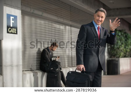 Smart businessman quickly getting ride from airport with smile and a wave - stock photo