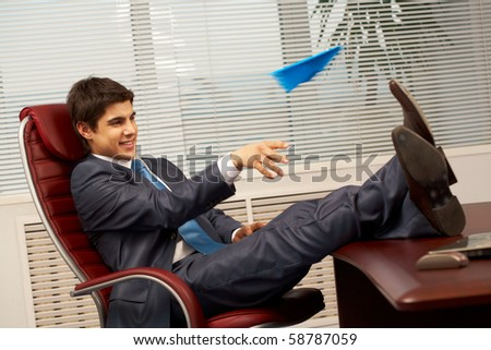 Smart businessman sitting in arm-chair in office and having fun during break - stock photo