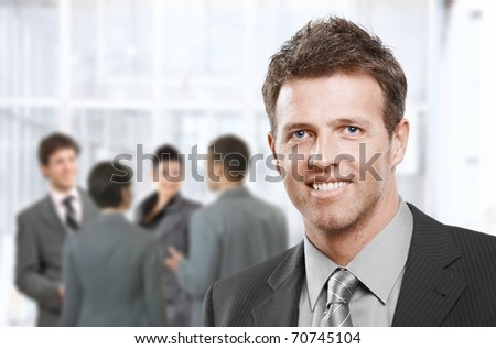 Smart businessman smiling at camera in closeup, colleagues talking in office lobby. - stock photo