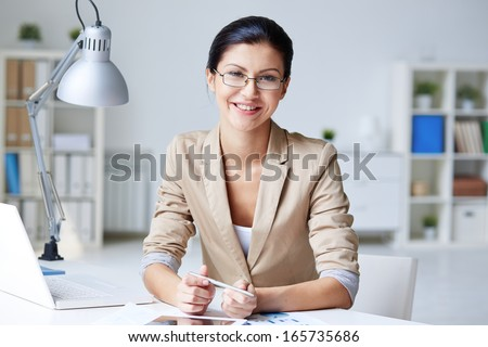 Smart businesswoman in formalwear looking at camera in office - stock photo