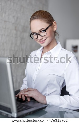 Smart businesswoman in glasses smile at laptop in office