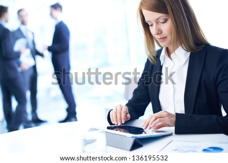 Smart businesswoman working with touchpad in working environment - stock photo
