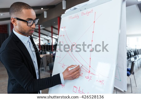 Smart concentrated businessman writing something on the flipchart using marker - stock photo