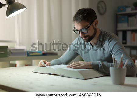 Smart confident young man studying late at night, he is sitting at desk and reading a book, knowledge and learning concept