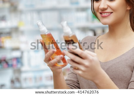 Smart decision. Cropped close up shot of a female customer smiling holding two medication bottles at the local drugstore. - stock photo