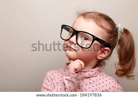 Smart dreaming kid girl in glasses looking. Closeup portrait - stock photo