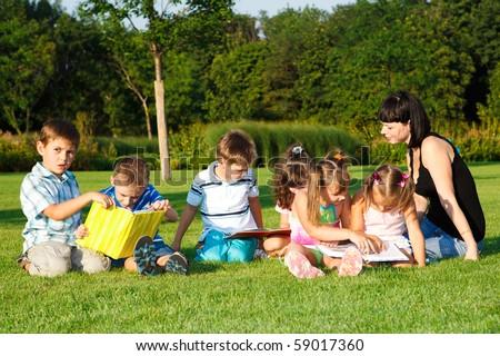 Smart elementary students reading books, teacher looks at them - stock photo