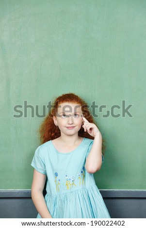 Smart girl thinking in elementary school class in front of chalkboard - stock photo