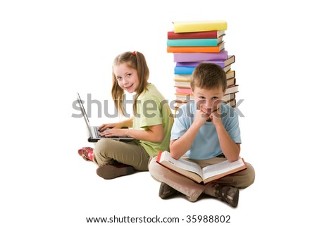 Smart girl with laptop and cute schoolboy with book sitting back to back and looking at camera - stock photo