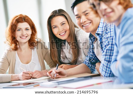 Smart groupmates looking at camera while sitting at lesson - stock photo