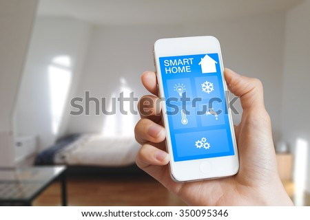 Smart home automation app on smartphone hold by female hand with home interior in background - stock photo