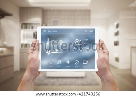 Smart home control on tablet. Interior of living room in the background. - stock photo