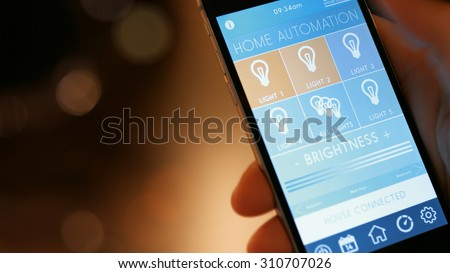 Smart house, home automation, device with App icons. Man uses his smartphone with smarthome app to control the lights of his house. - stock photo