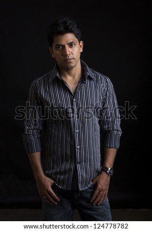 Smart Indian young man against on black background. - stock photo