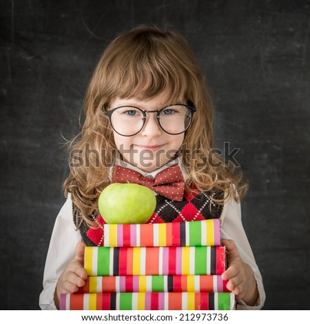 Smart kid in class. Happy child against blackboard. Education concept - stock photo