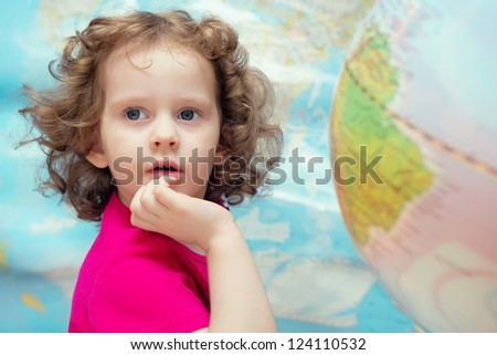 Smart little girl looks closely, the picture on the background of the world map and globes - stock photo