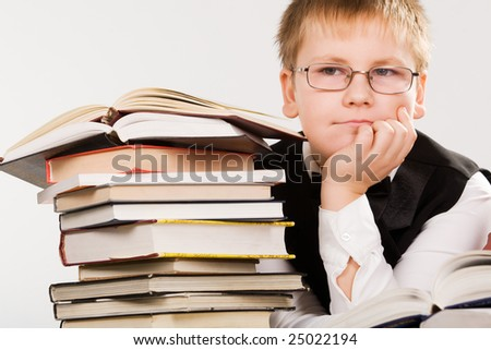 smart looking school boy reading a book, isolated on white