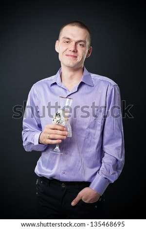 Smart man drinking champagne. A male wearing  tie raising a glass of champagne, isolated on a black background.
