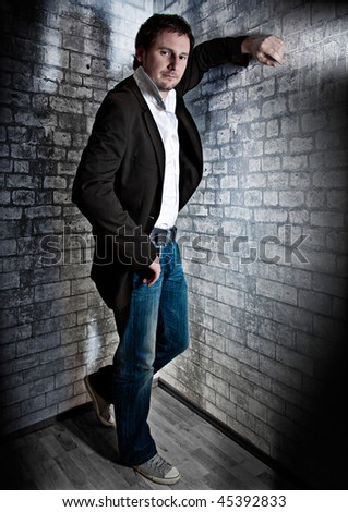 smart man leaning against a wall