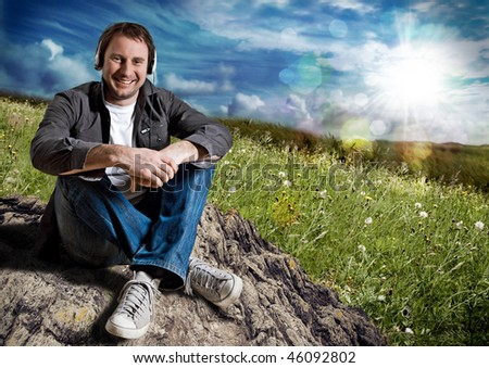 smart man relaxing in a meadow and listening to music - stock photo