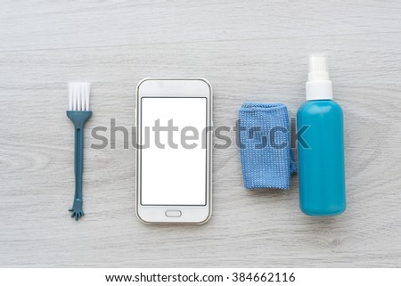 Smart phone and cleaing set on gray background. - stock photo