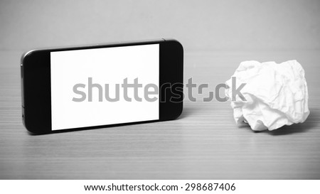 smart phone and crumpled paper on wood background black and white color tone style