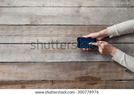 smart phone and girl holding it over a wooden table - stock photo