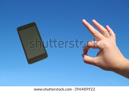 smart phone and okay gesture in the blue sky