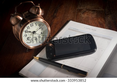 Smart phone and pen on plan book with alarm clock. - stock photo