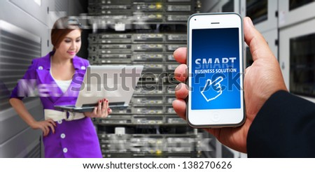 Smart phone and programmer in data center room - stock photo