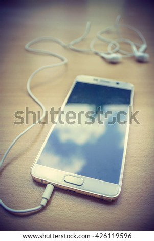 smart phone and white earphone on wood table in retro filter - stock photo