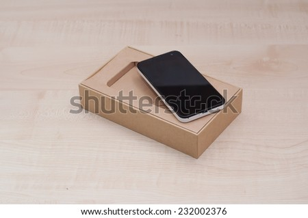 Smart Phone In Packaging Box on the table - stock photo