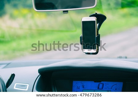 Smart phone in the car holder on the windshield